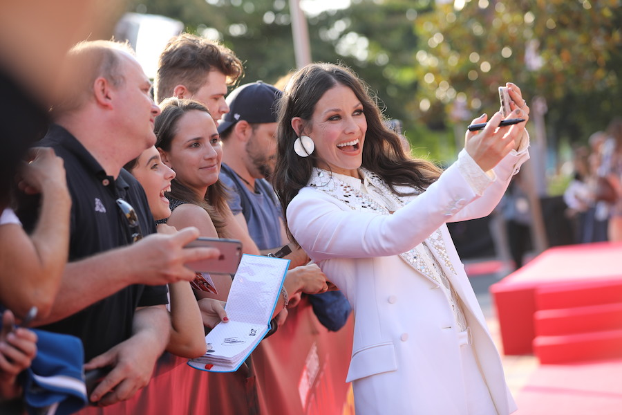 Actress Evangeline Lilly poses for a selfie with fans during the European Premiere of Marvel Studios
