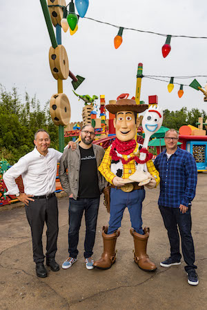 Director Josh Cooley (center left) with Producers Jonas Rivera (left) and Mark Nielsen (right) appear with Woody and Forky (center right) inside Toy Story Land at Disney's Hollywood Studios