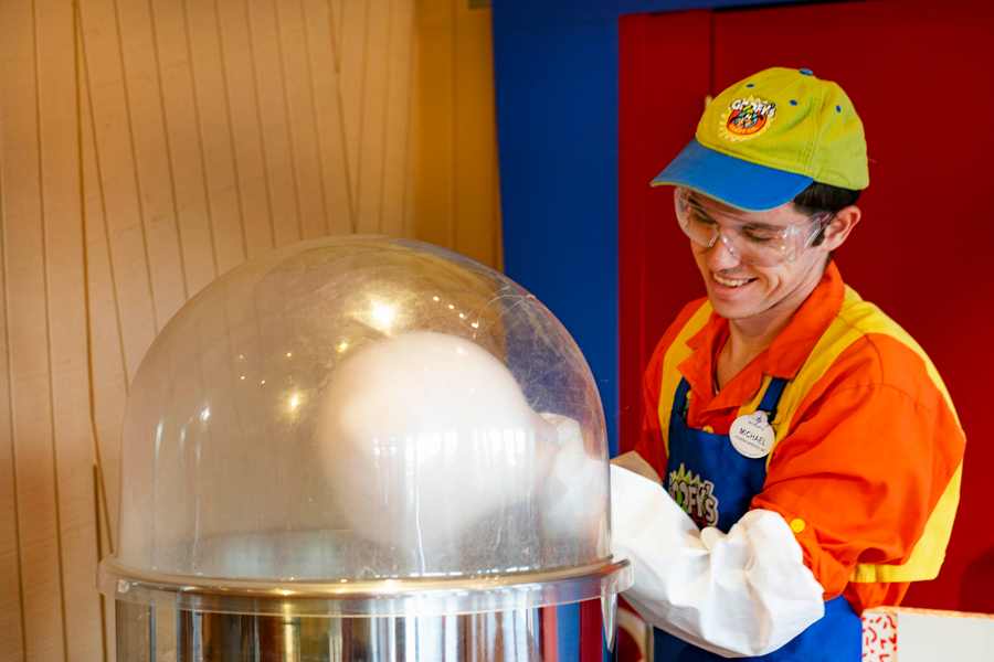 Cast member makes cotton candy at Goofy's Candy Co. at Disney Springs