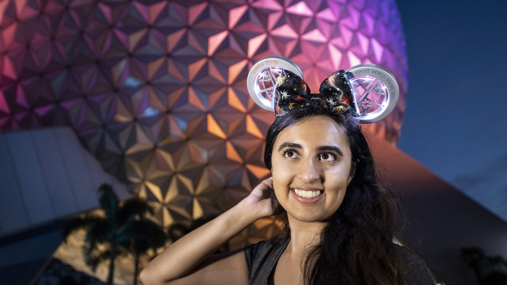 Woman wearing the light-up Minnie Mouse ear headband celebrating 'IllumiNations Reflections of Earth'