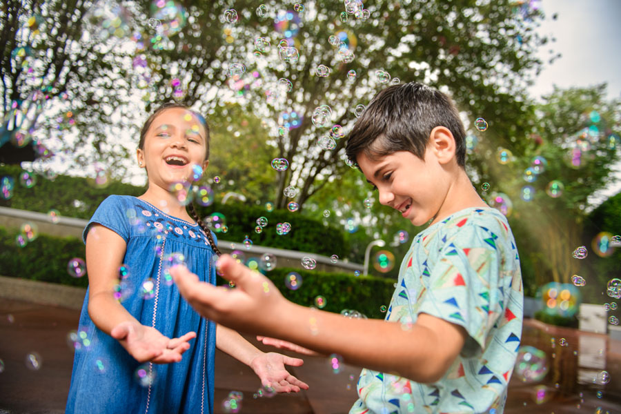 Kids play with bubbles in a Disney PhotoPass photo at Magic Kingdom Park